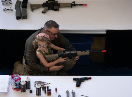 A man shows a girl how to hold an airsoft gun during the NRA Youth Day at the National Rifle Association's annual meeting in Houston, Texas